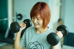 Гантели тайской дамы поднимаясь в спортзале Стоковые Изображения