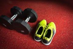 Гантели фитнеса с ботинками спорта в спортзале Стоковое Изображение