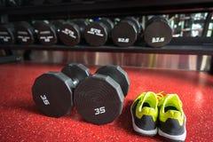 Гантели фитнеса с ботинками спорта в спортзале Стоковые Изображения