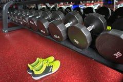 Гантели фитнеса с ботинками спорта в спортзале Стоковые Изображения RF