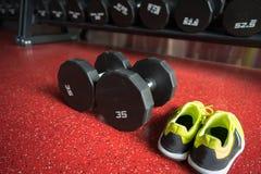 Гантели фитнеса с ботинками спорта в спортзале Стоковое Изображение RF