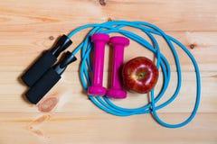 Гантели, яблоко и прыгая веревочка на деревянной предпосылке Стоковое Фото