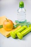 Гантели, яблоко, полотенце и бутылка воды Стоковая Фотография RF