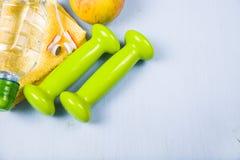 Гантели, яблоко, полотенце и бутылка воды Стоковое фото RF
