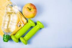 Гантели, яблоко, полотенце и бутылка воды Стоковая Фотография