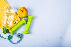 Гантели, яблоко, полотенце и бутылка воды Стоковые Изображения RF