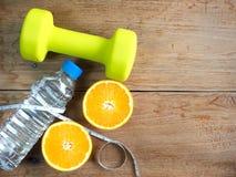 Гантели, апельсин, бутылка воды и измеряя лента для фитнеса Стоковая Фотография RF