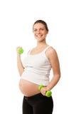 Гантели беременной девушки поднимаясь изолированные на белизне Стоковое Фото