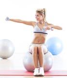 Гантели женщины поднимаясь пока сидящ на шарике фитнеса Стоковая Фотография