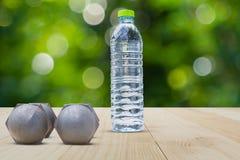 Гантели и взгляд со стороны бутылки с водой на деревянном поле на запачканной предпосылке bokeh Стоковые Фотографии RF