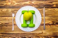 Гантели и яблоко на плите как завтрак, концепция здорового образа жизни Стоковые Изображения RF