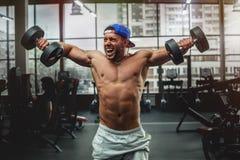 Гантели красивого человека поднимаясь на спортзале Стоковое Фото