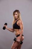 Гантели красивой женщины фитнеса поднимаясь Sporty девушка показывая ее вышколенное тело изолированный на серой предпосылке с Стоковые Изображения RF