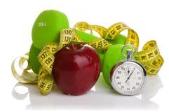 2 гантели, красное яблоко, измеряя лента Стоковая Фотография