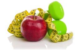 2 гантели, красное яблоко, измеряя лента Стоковое Фото