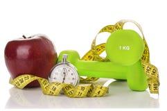 2 гантели, красное яблоко, измеряя лента Стоковое Изображение