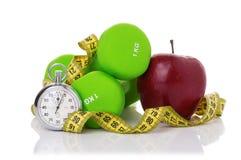 2 гантели, красное яблоко, измеряя лента Стоковые Фото