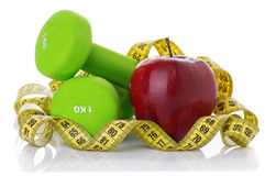 2 гантели, красное яблоко, измеряя лента Стоковые Изображения