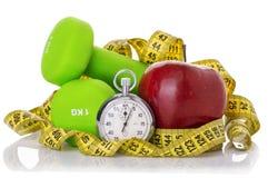 2 гантели, красное яблоко, измеряя лента Стоковое фото RF