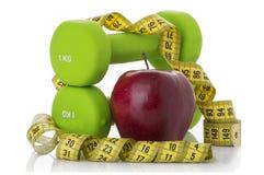 2 гантели, красное яблоко, измеряя лента Стоковые Изображения RF