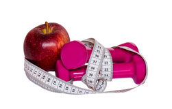 Гантели, красное яблоко и лента измерения изолированные на белизне Стоковые Изображения