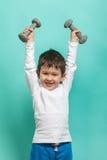 гантели мальчика немногая Здоровый уклад жизни Спорт и деятельность для детей Стоковые Фото