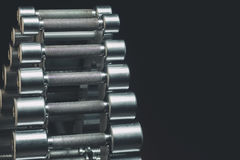 Гантели металла на железной стойке в зале спорт, конце-вверх на черной предпосылке Стоковые Фотографии RF