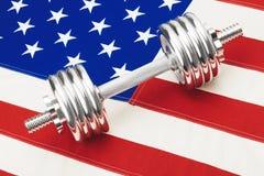 Гантели металла над флагом США как символ здоровой нации - близкой поднимающей вверх съемки студии Фильтрованное изображение: вли Стоковые Изображения