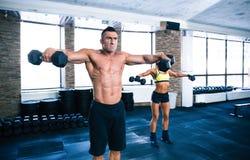 Гантели мышечного человека и sporty женщины поднимаясь Стоковые Изображения