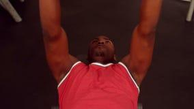 Гантели мышечного человека поднимаясь пока лежащ на стенде видеоматериал