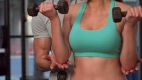 Гантели мышечной женщины поднимаясь сток-видео