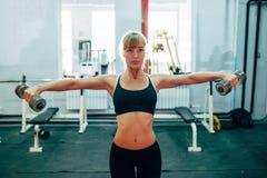 Гантели повышения женщины на спортзале Стоковые Изображения RF