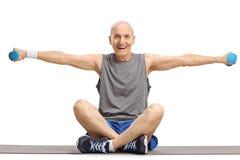 Гантели пожилого человека поднимаясь и сидеть на циновке тренировки Стоковое фото RF