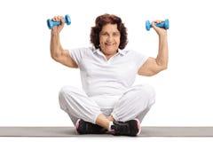 Гантели пожилой женщины поднимаясь на циновке тренировки Стоковые Фотографии RF