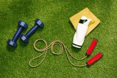 Гантели, полотенце и бутылка с веревочкой скачки в форме слова идут Стоковое фото RF