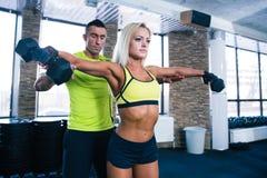 Гантели подходящей женщины поднимаясь с тренером Стоковое Изображение RF