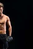Гантели сильного мужского спортсмена поднимаясь Стоковые Изображения RF