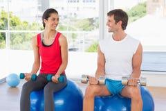 Гантели счастливых пар поднимаясь пока сидящ на шариках фитнеса в спортзале Стоковая Фотография RF