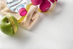 Гантели с бутылкой и рулеткой яблока и повышенное полотенце Стоковые Фотографии RF