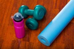 2 гантели с бутылкой с водой и циновкой йоги, sporty концепцией образа жизни Стоковое Изображение RF