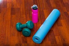 2 гантели с бутылкой с водой и циновкой йоги, sporty концепцией образа жизни Стоковое Фото