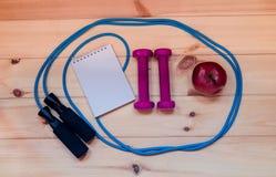 Гантели, тетрадь, яблоко и прыгая веревочка Стоковые Изображения RF