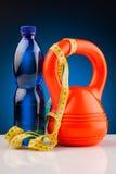 Гантели фитнеса и бутылка воды Стоковые Изображения