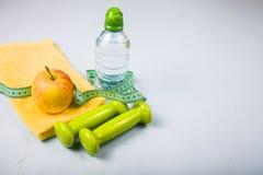Гантели, яблоко, полотенце и бутылка воды Стоковые Фото