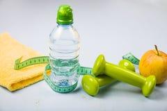 Гантели, яблоко, полотенце и бутылка воды Стоковые Фотографии RF