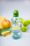Гантели, яблоко, полотенце и бутылка воды Стоковое Фото