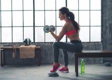 Гантель женщины фитнеса поднимаясь в городском спортзале просторной квартиры стоковая фотография rf