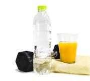 Гантель и апельсиновый сок изолированные на белой предпосылке Стоковая Фотография