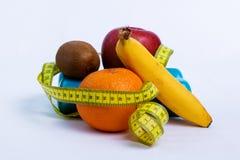 Гантель и яблоко, апельсин, банан, предпосылка белизны кивиа стоковое изображение rf