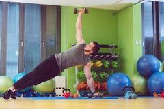 Гантель молодого человека поднимаясь на фитнес-центре стоковое изображение rf